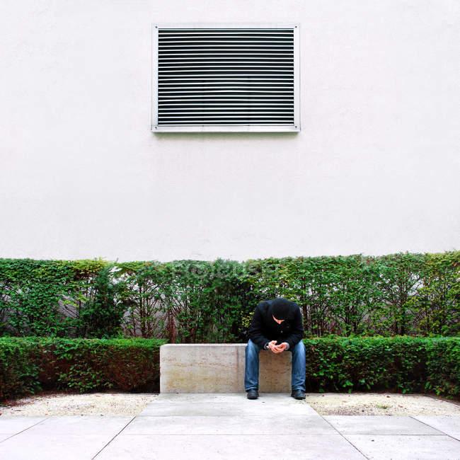 Mann, sitzen auf einer Steinbank im Laufe des Tages — Stockfoto