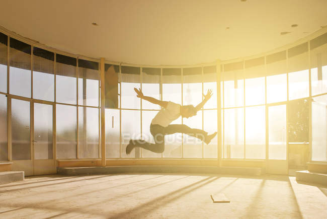 Action shot of a man jumping against a window with sunlight streaming through — Stock Photo