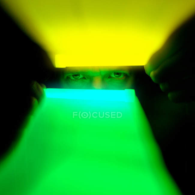 Close-up retrato de um homem usando iluminado iluminação em um quarto escuro — Fotografia de Stock