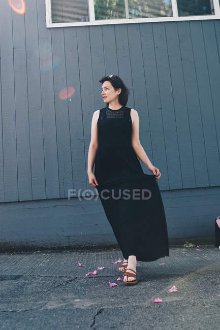 Full length of young woman standing outside against wall in black dress — Stock Photo