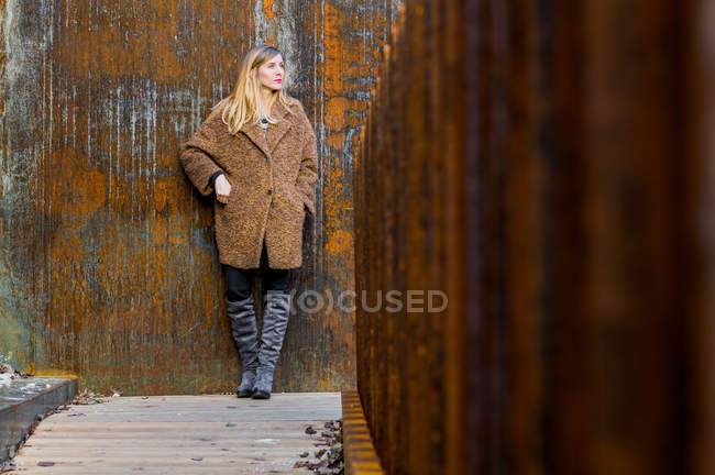 Woman in warm clothing standing against a wall — Stock Photo