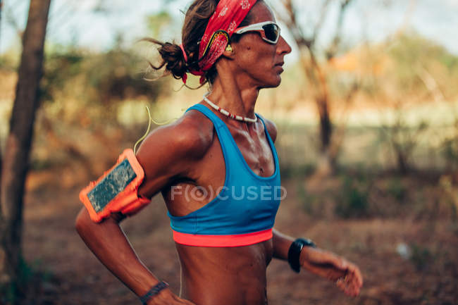 Side view of young sporty female runner — Stock Photo