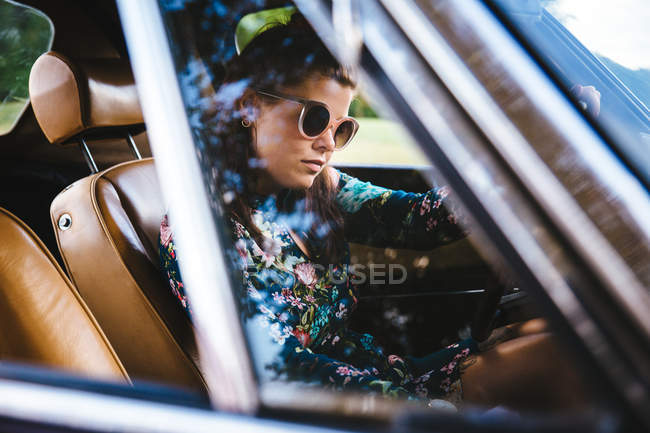 Young woman wearing sunglasses driving — Stock Photo