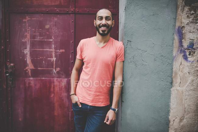 Handsome Hispanic bearded man in casual clothing posing at building wall and door — Stock Photo