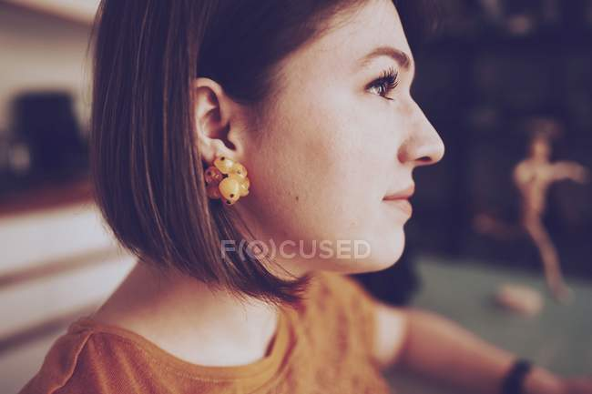 Brunette young woman in profile, wearing yellow earrings and yellow blouse — Stock Photo