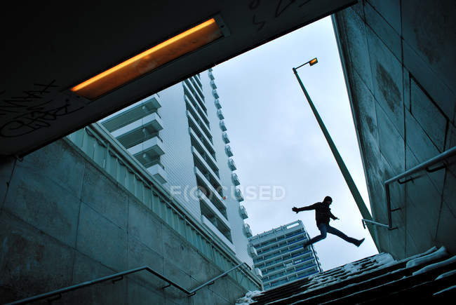 Low angle view of a man in mid air under a grey sky in Berlin, Germany — Stock Photo