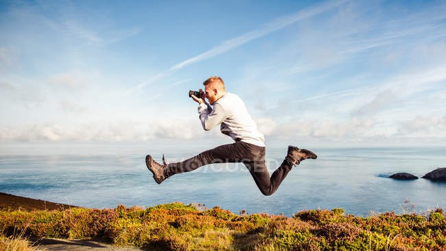 Action shot of a man jumping in the air while taking a photograph — Stock Photo