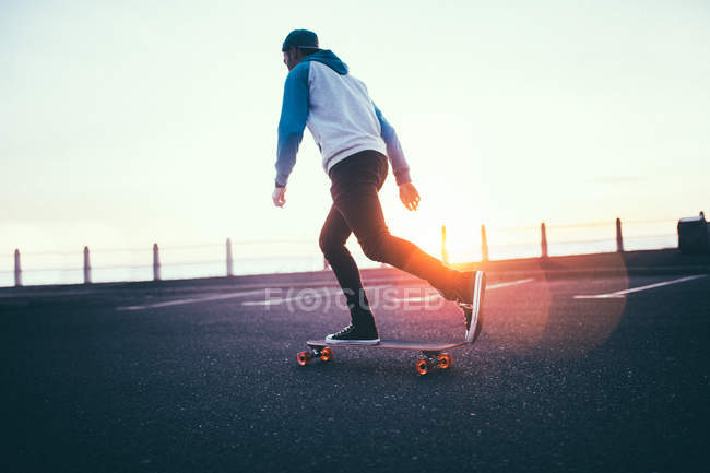 Young adult man riding longboard at promenade at sunset — Stock Photo