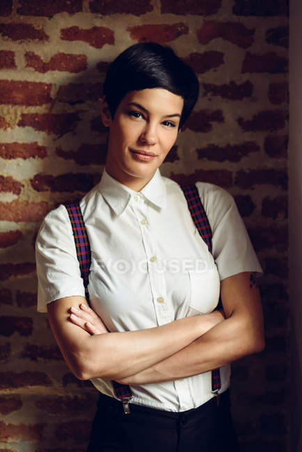 Woman with short hair wearing shirt with suspenders and posing at brick wall — Stock Photo