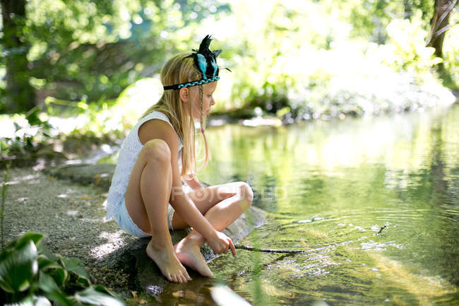 Young blonde girl sitting by lake — Stock Photo