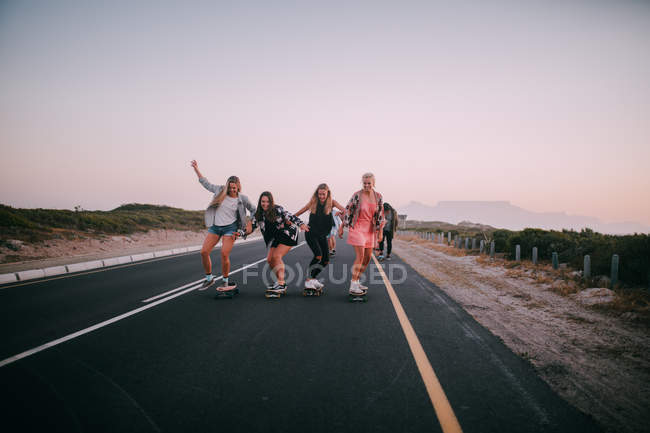 Group of young adult friends cheering and riding longboards — Stock Photo