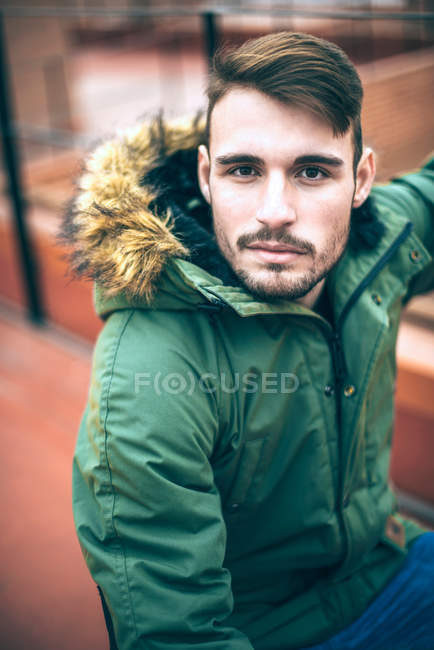 Handsome model man in green parka jacket posing outdoors — Stock Photo