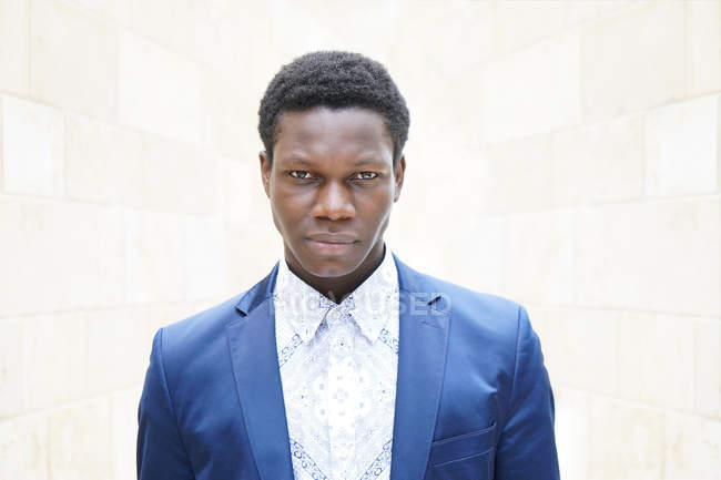 Handsome african man in blue suit jacket looking at camera — Stock Photo