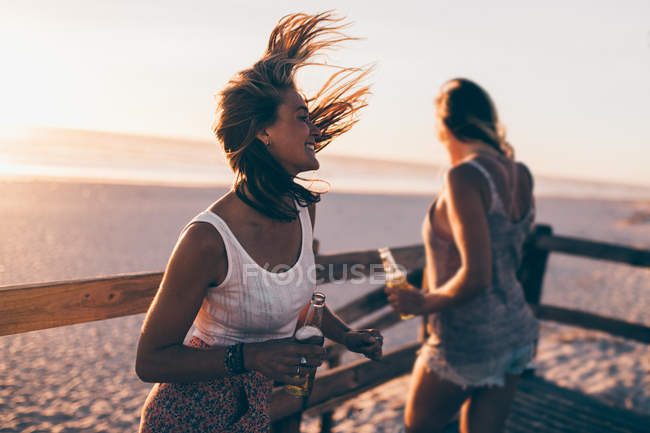 Friends dancing at a summer sunset beach party — Stock Photo
