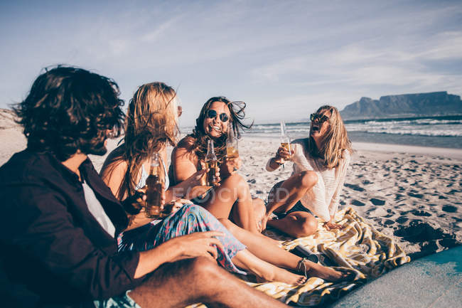 Young friends sitting at the beach together — Stock Photo