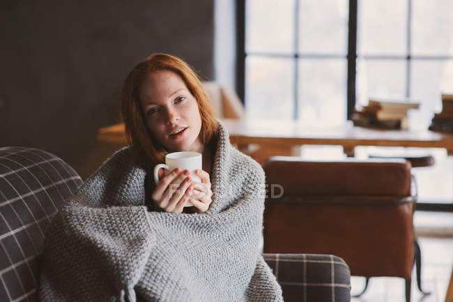 Portrait of young woman drinking coffee at home and covered with warm knitted blanket — Stock Photo
