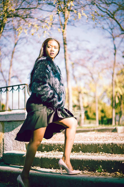 Gorgeous African woman in fur coat walking on stairs outdoors in park — Stock Photo