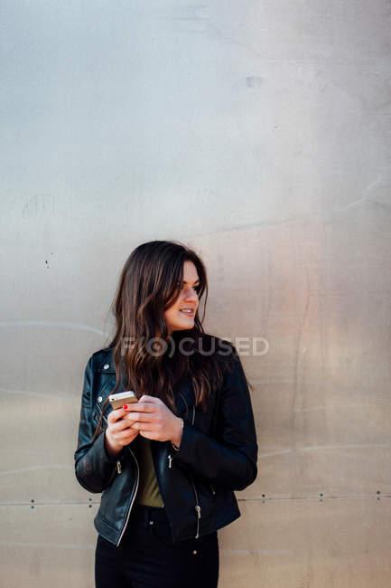 Молода жінка носить шкіряна куртка за допомогою смартфона — стокове фото