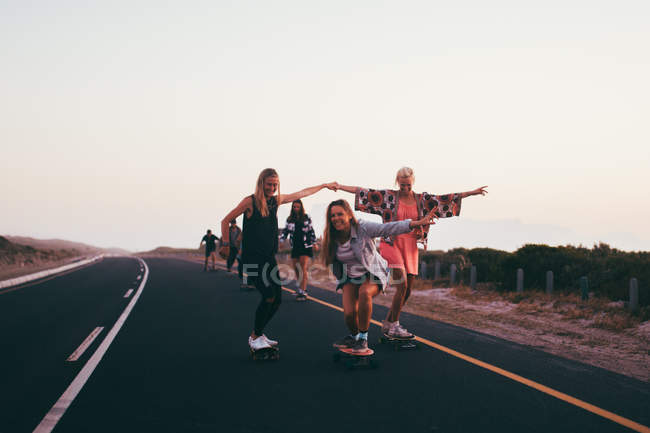 Young adult group of friends riding longboards on road together — Stock Photo