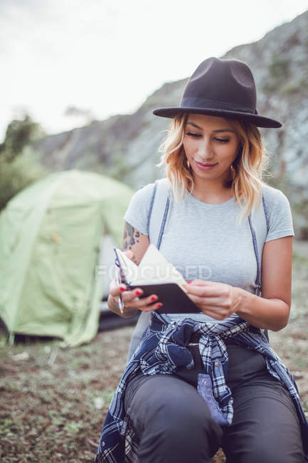 Woman in hat writing notes in diary while traveling and camping with tent — Stock Photo