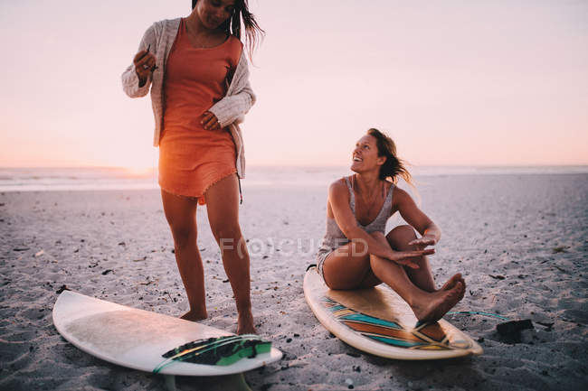 Friends on the beach against a clear sky during sunset — Stock Photo