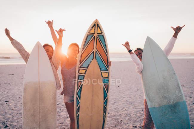 Three female friends at the beach against a sunny sky — Stock Photo