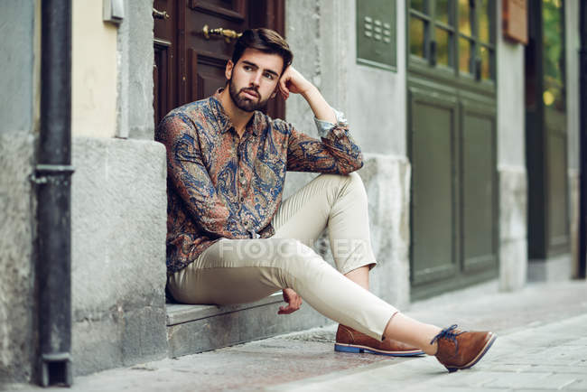 Stylish Hispanic young man sitting outdoors at house door — Stock Photo