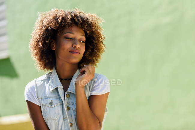 Young woman with afro hairstyle smiling outdoors — Stock Photo