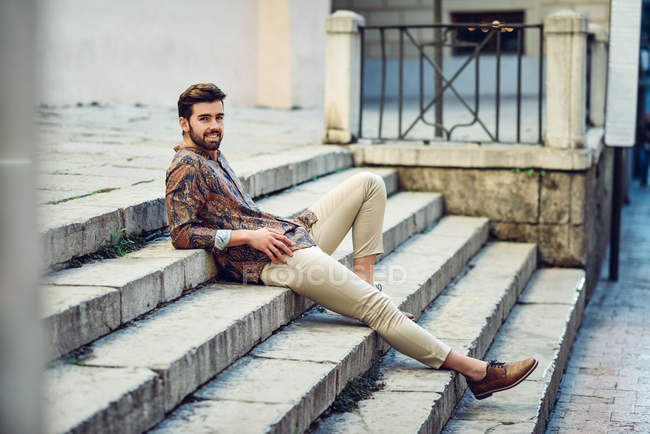 Stylish young man sitting on steps in street — Stock Photo