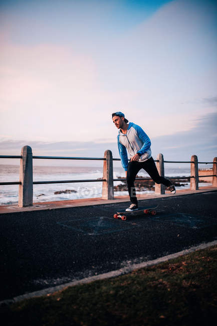 Young adult man riding longboard at promenade — Stock Photo