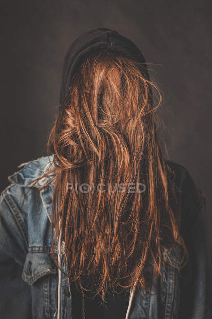 Back to front view of woman with face covered by hair standing against wall. — Stock Photo