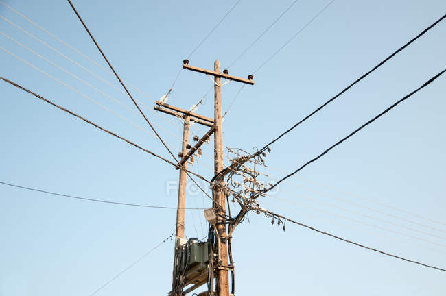 Low angle view of an electricity pylon under blue skies — Stock Photo
