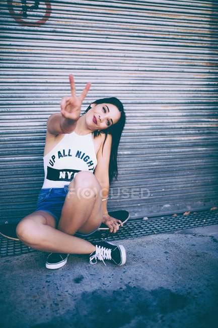 Mulher sentada no skate e gesticulando sinal de paz com os dedos — Fotografia de Stock