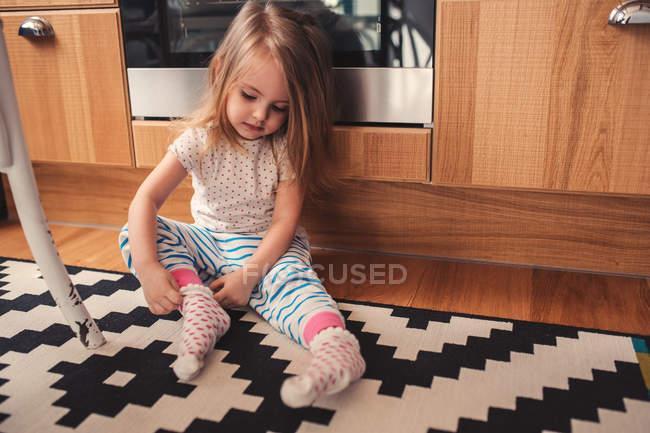 Caucasica adorabile bambina che si siede sulla moquette del pavimento a casa e vestire calzini — Foto stock