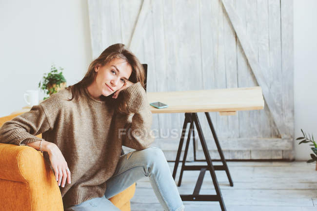 Caucasian thoughtful young woman on orange arm chair at home — Stock Photo