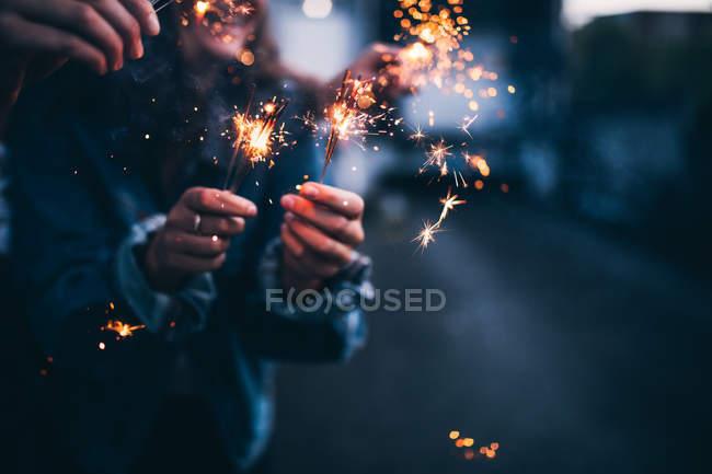 Hand holding sparkler in the evening light — Stock Photo