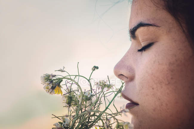 Head shot of woman with closed eyes smelling field flowers — Stock Photo