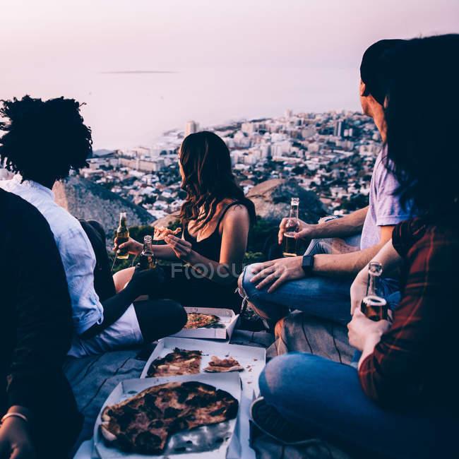 Gruppe von Freunden mit Picknick zusammen während des Sonnenuntergangs — Stockfoto