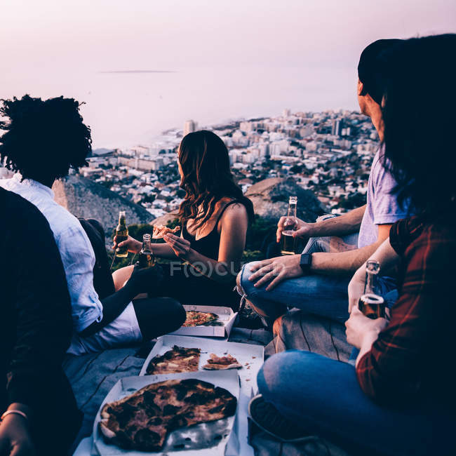 Group of friends having picnic together during sunset — Stock Photo