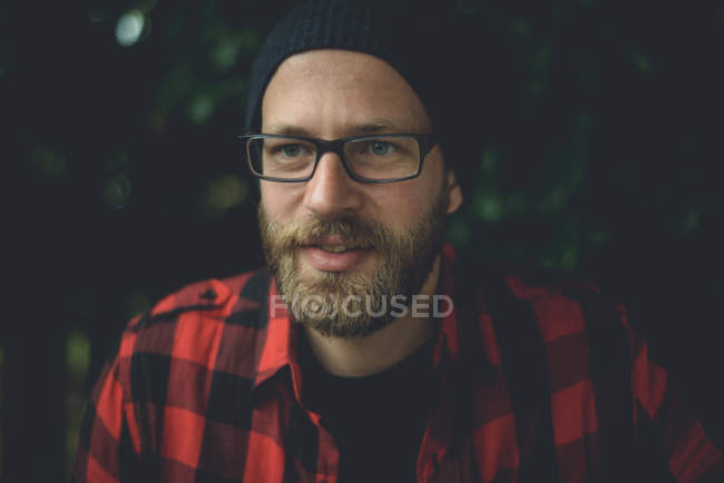 Handsome man with beard wearing hat and red plaid shirt — Stock Photo