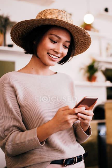 Giovane donna asiatica nel messaggio SMS cappello con telefono — Foto stock
