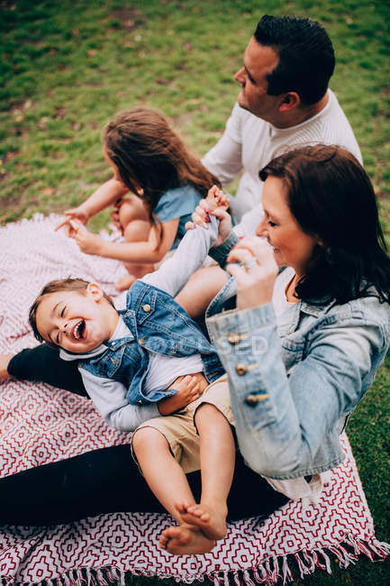 Family of four having fun on a picnic mat in the park — Stock Photo