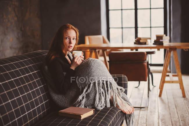 Joven mujer sentada en el sofá con la taza de té y manta - foto de stock