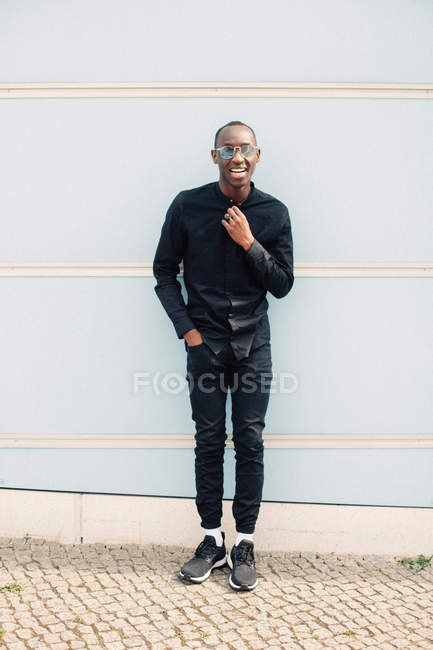Full body portrait of happy casual black man standing against white wall — Stock Photo