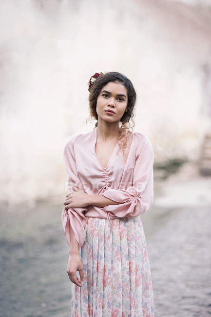Portrait of beautiful young woman standing outdoors and wearing vintage pink dress — Stock Photo