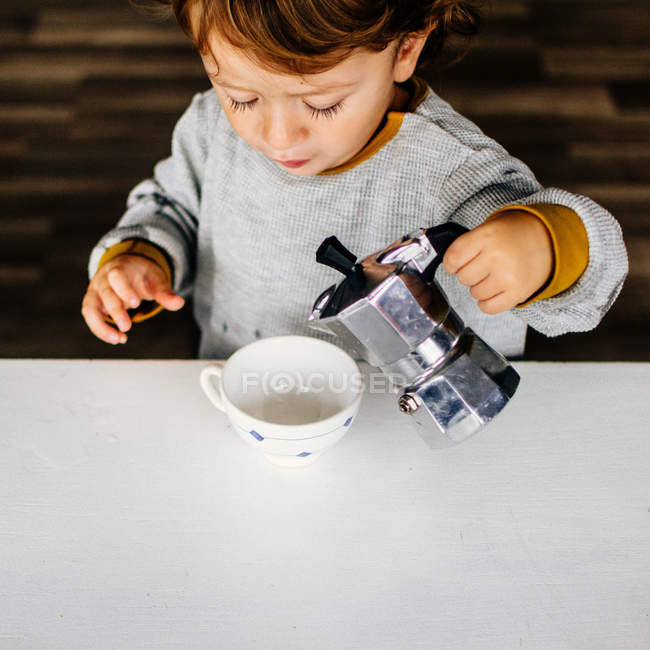 Close-up of boy pouring coffee from moka pot — Stock Photo