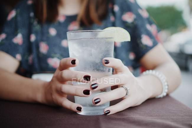 Woman holding iced glass of water — Stock Photo