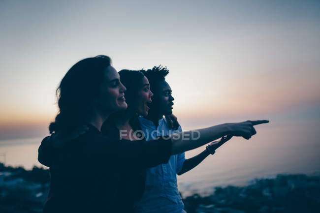 Friends having fun on mountains against evening sky — Stock Photo