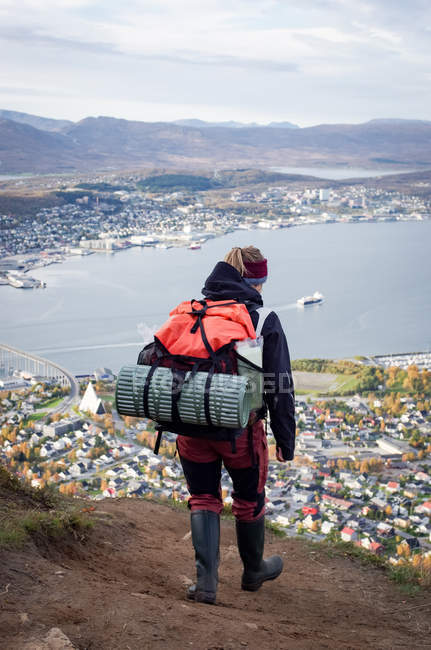 Rear view of woman looking at port city in mountains with lake, Scandinavia — Stock Photo