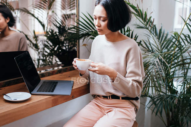 Confident young Asian businesswoman drinking coffee in cafe with laptop on table — Stock Photo